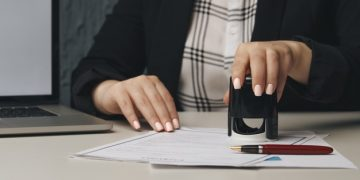 close-up-woman-s-notary-public-hand-stamping-document-notary-public-concept_253401-2431